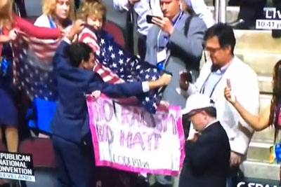 "Woman Trying To Hold A Sign ""No Racism No Hate"" Being Covered By Trump Supporters"