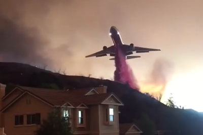 An Airplane Dropping A Massive Ploom Of Fire Retardant Powder Over Sand Fire In California