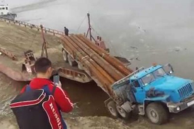 Construction Truck Loaded With Massive Metal Pipes Tumbles Into A River