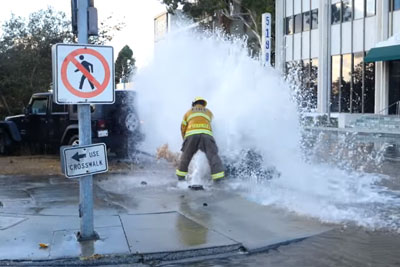 Fireman Shuts Off Fire Hydrant After Jeep Hits It