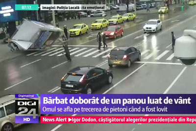 Wind Blows Street Sign Over Crossing Pedestrian In Romania