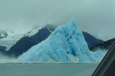 Iceberg Rolls Over In The Sea Infront Of Tourists