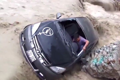 Driver Escapes From Car Stuck In Peru Floodwaters