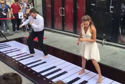 Couple Steps Up To Floor Piano. Plays Classic Tune That Has Crowd Instantly Cheering