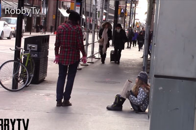 Young Homeless Girl Sits Alone Begging For Help. Pay Close Attention To Woman In Red Plaid