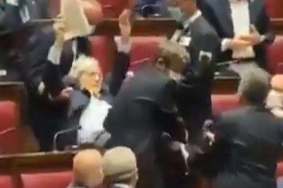VIDEO: Italijanskega politika odnesli iz parlamenta, ker ni imel maske